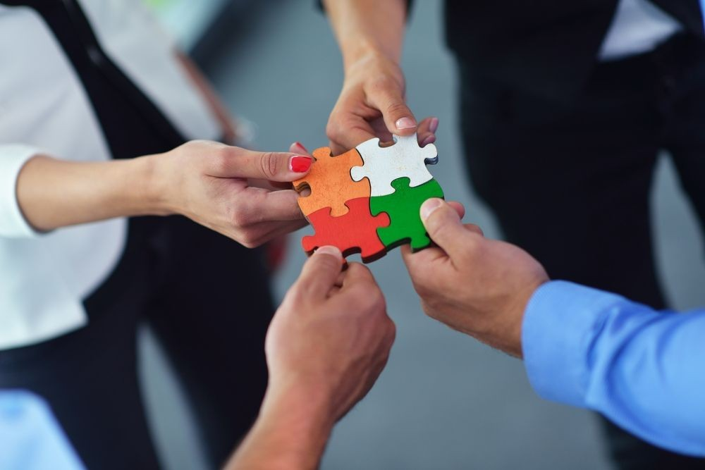 Group-of-business-people-assembling-jigsaw-puzzle-and-represent-team-support-and-help-concept